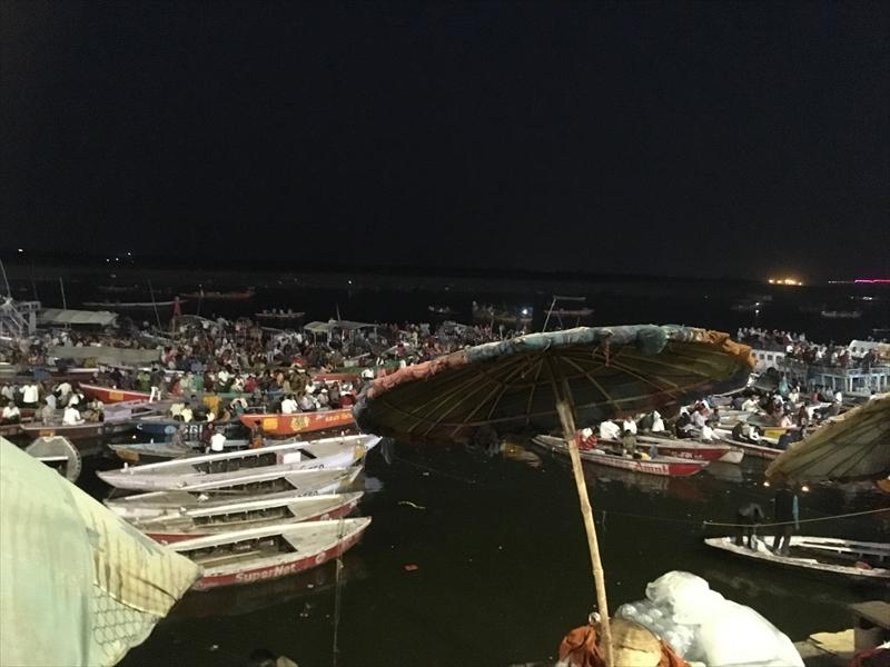 ガンジス川の岸辺からボートに乗って「プージャ/アールティ」に参加する人々